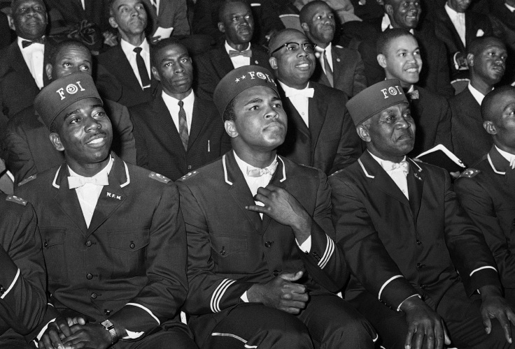 1966 file photo, Muhammad Ali listens to Elijah Muhammad as he speaks to other black Muslims in Chicago.