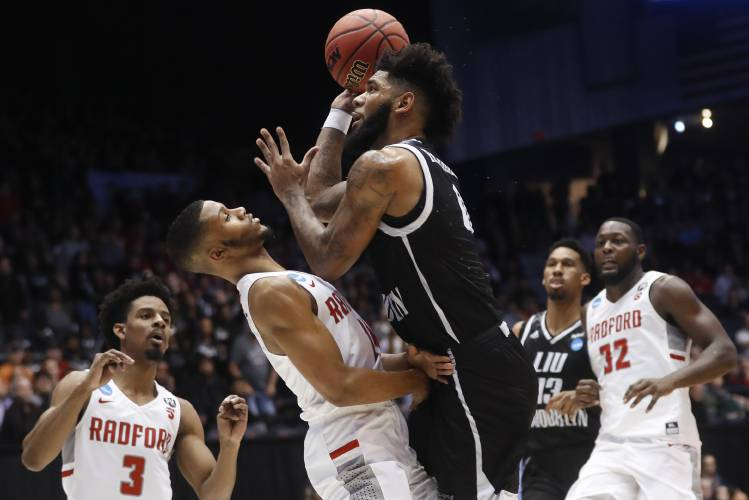 Center Right Shoots Against Radfords Travis Fields Jr During The First Half Of A First Four Game Of The Ncaa Mens College Basketball Tournament