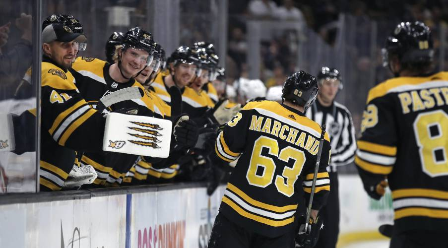 86c8f78c478 Boston Bruins left wing Brad Marchand (63) is congratulated after his  second period goal against the Arizona Coyotes during an NHL hockey game in  Boston
