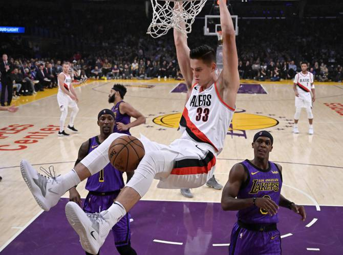 9c00364bf0b9 Portland Trail Blazers forward Zach Collins hangs from the rim after a  dunk