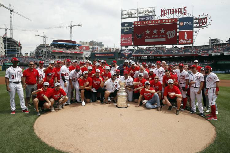 b8baeb072 The Washington Capitals and the Washington Nationals pose for a group photo  on the field with the Stanley Cup before a baseball game between the  Nationals ...