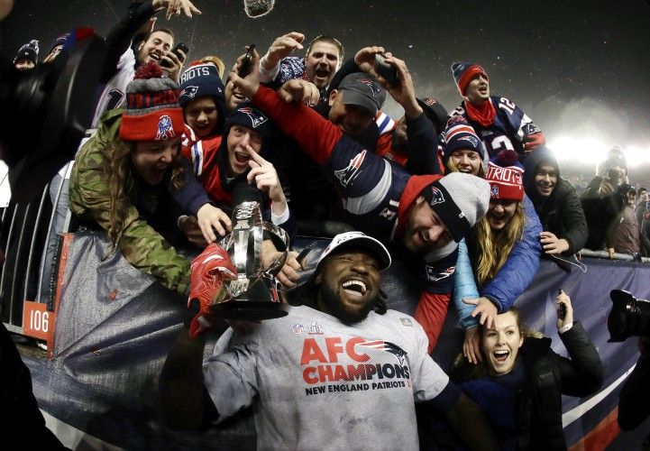 d12b6b228 New England Patriots running back LeGarrette Blount holds the AFC  championship trophy surrounded by fans after the AFC championship NFL  football game