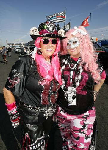 ccaf3304910 Fans wear pink for cancer awareness while tailgating before an NFL football  game between the Oakland Raiders and the Los Angeles Chargers in Oakland,  ...